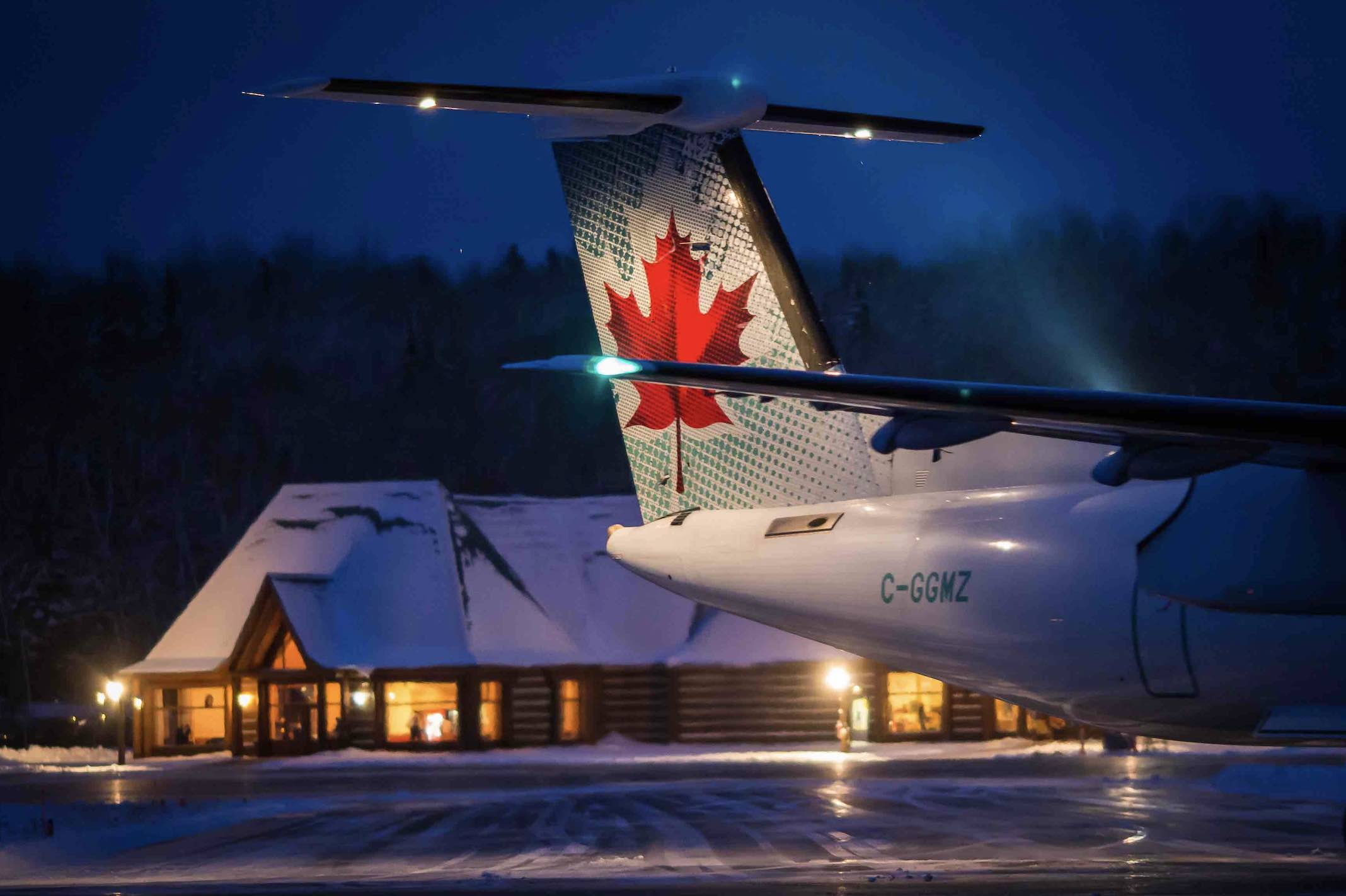 Air Canada jet sitting at airport in Mont-Tremblant at night