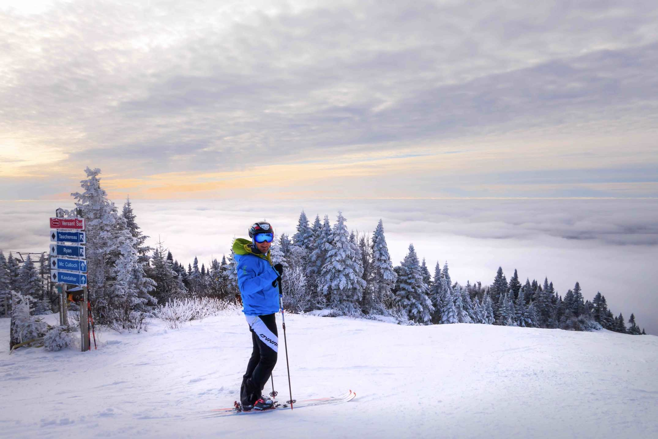 Tremblant winter things to do in Mont Tremblant with skiier at top of the mountains above clouds