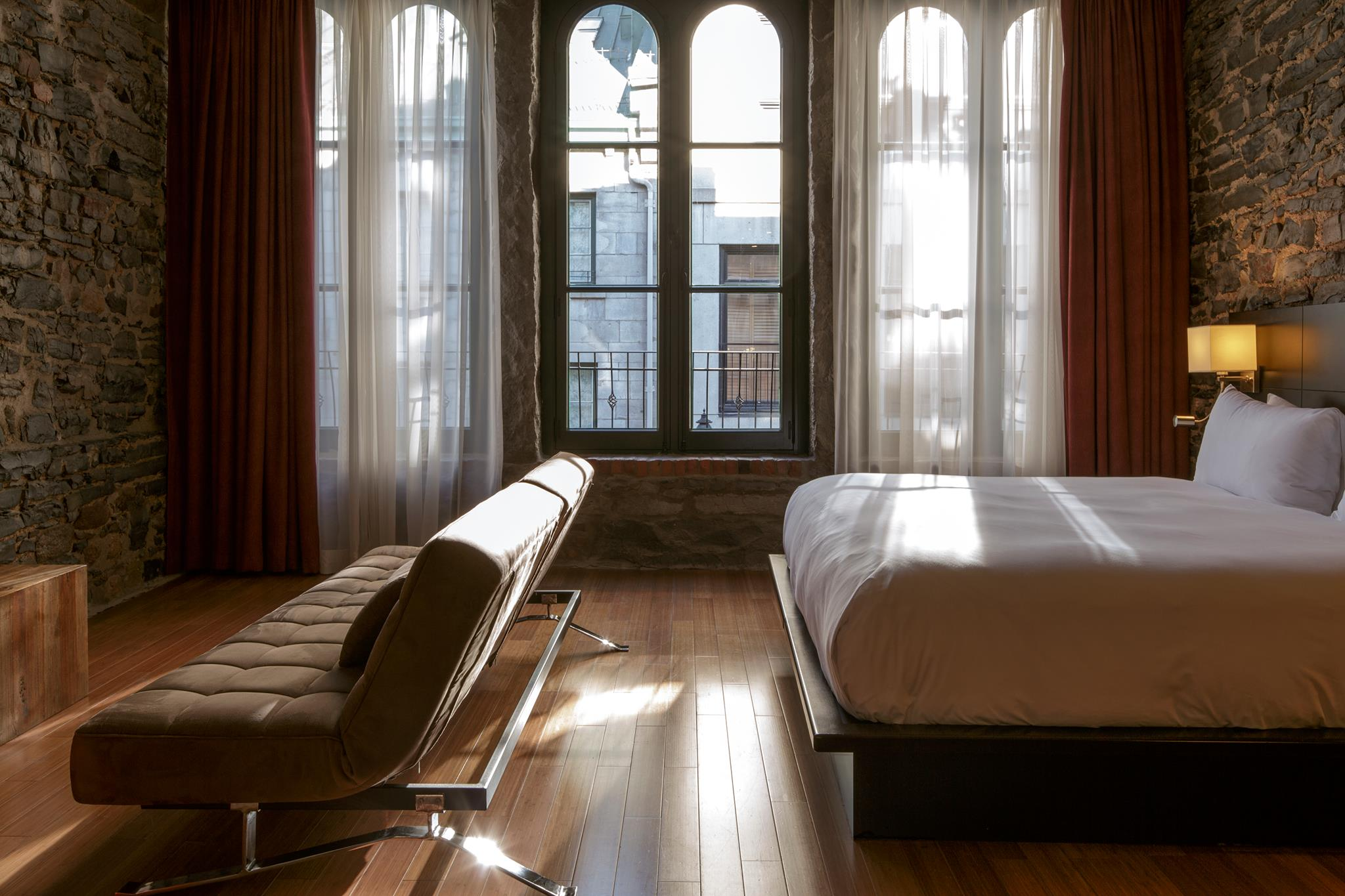 Le Petit Hôtelbedroom of boutique hotels in montreal with old exposed wlla and city view